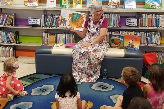 Woman reading a book to children.