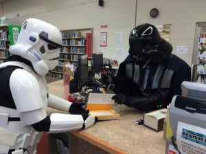 People dressed in star wars costumes checking out a book
