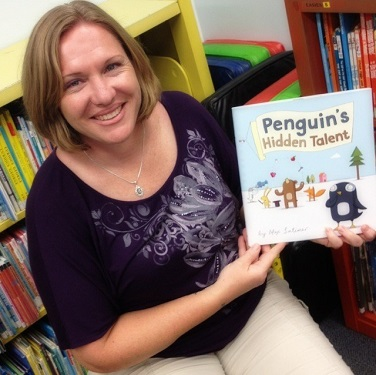 Woman holding a book called 'Penguins hidden talent'