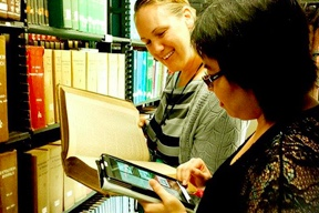 Two women looking at a book and ipad in a library book aisle