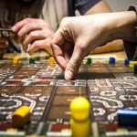Hand moving a game piece in a board game.