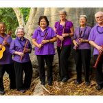 Group of 6 people standing in front of a tree. Five people are holding recorders. One person is holding a 'ukelele.