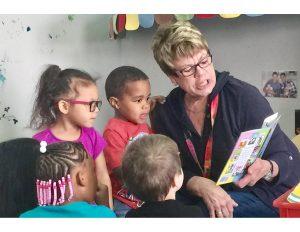 Adult reading to three children