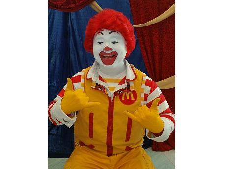 Ronald McDonald sitting with shaka hand gestures