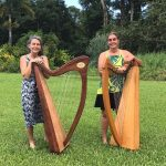 Two harpists on grass lawn