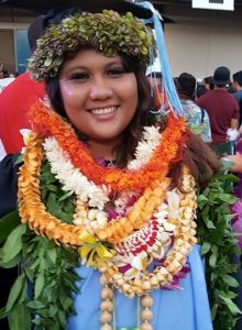 Woman wearing leis in graduation photo and smiling