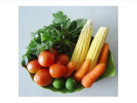 Photo of bowl containing 2 ears of corn, 4 carrots, 6 tomatoes, 2 avocados, and leafy vegetables.