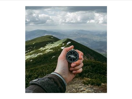 photo of hand holding wrist compass overlooking mountain terrain