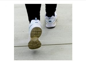 Photo of pair of walking shoe-clad feet with right foot forward and left heel raised.