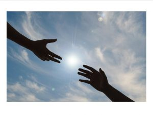Photo of 2 hands reaching toward each other against a background of blue sky and white clouds.