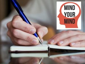 "Photo of person's hands writing in a journal and ""Mind Your Mind"" logo"