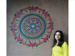 Artist Ayala Wise standing in front of a red, aqua and purple mandala painted on a wall