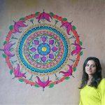 Artist Ayala Wise standing next to large mandala