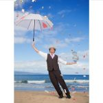 man with umbrella standing on beach with cards flying all around