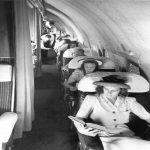 Retro picture of passengers reading on a Pan Am Boeing 207