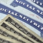 Social Security cards with several hundred dollar bills