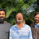 Three bearded men laughing with a background of areca palms