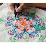 Artist drawing a colorful Mandala on a reusable bag