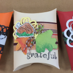 three pillow box gift holders. an orange and black with a ghost and the word BOO; one tan and brown with a picture of a cooked turkey and the word GRATEFUL; one is red with a green holly branch and cup of hot chocolate with marshmallows
