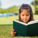 young girl reading in a park