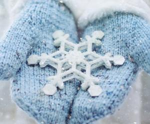 Blue mittens holding a large snowflake