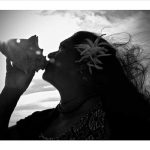 woman blowing conch shell