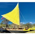 double hull canoe with a yellow sail