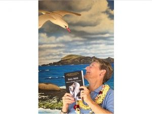 Woman looking up at an albatross while holding a book