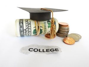 Graduation cap with money roll and coins