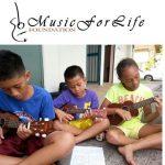 Three children sitting and playing the ukulele