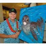 Portrait of the artist in front a Hawaiian Monk Seal painting
