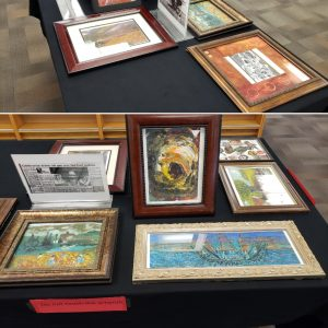 seven oil on canvas paintings in frames on a black tablecloth