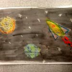 Crayon solar system drawing with ink background