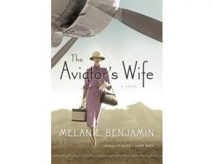 cover of book The Aviator's wife; woman with luggage walking under airplane rotor