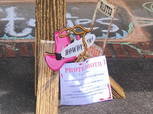 Western-themed photo props, including pink cowboy hat and wanted poster cut-out.
