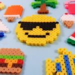 several perler bead designs to include: a hamburger, sailboat, ice cream, palm tree, smiley face, fish, and water melon