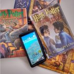 Harry Potter books with cell phone opened to Wizards unite game