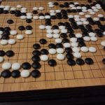black and white go game pieces on a board