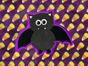 black bat sticker on candy corn background
