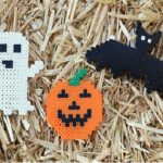 Perler bead creations in halloween shapes that include a ghost, a jack o lantern, and a bat.