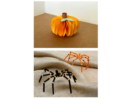 a paper pumpkin and two pipecleaner spiders