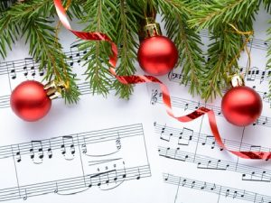 Sheet music with holiday ornaments and pine tree branches