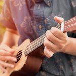 Male playing an ukulele
