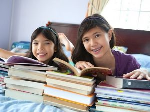 Two girls reading books on a bed