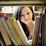 Female Teen looking at books in library