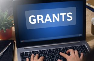 Laptop computer with the word Grants on screen