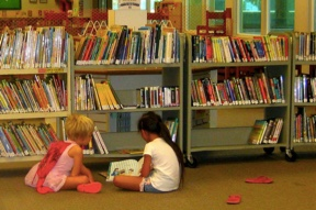 Kids reading in front of a bookshelf stuffed with books
