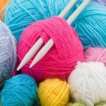 Knitting needles surrounded by balls of colorful yarn.