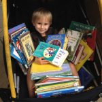 Child in stroller holding lots of books