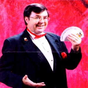 Magician Glen Bailey holding a deck of cards in left hand.